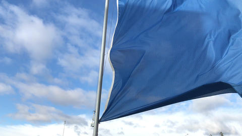 Blue flag waving against blue sky with clouds at windy day Live Action