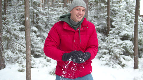 Man in winter gloves sculpts a snowball. Medium shot Live Action