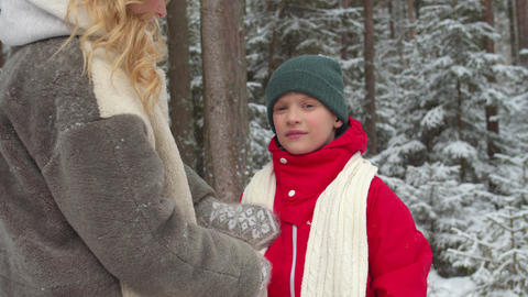 Loving mom puts a scarf on her son. Medium shot Live Action
