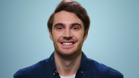 Handsome man smiling on blue background. Smiling guy standing in studio Live Action