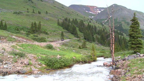 A jeep drives through wilderness in the Colorado R Stock Video Footage