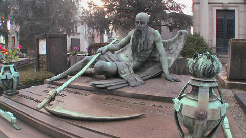 The grim reaper sits on a tomb in a graveyard with Footage