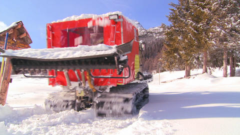 A small snow cat moves down a snowy road Stock Video Footage
