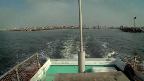 A boat sails away from shore, with a city in the distance Footage