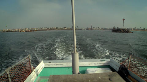 A boat sails away from shore, with a city in the distance Stock Video Footage