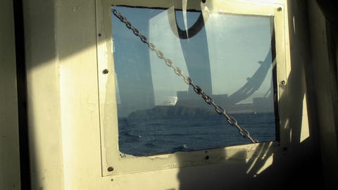 An island is viewed through a boat window Stock Video Footage