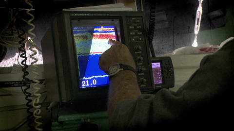 A man points to a sonar display on a small vessel Footage