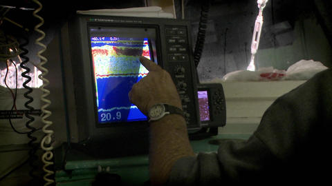 A man points to a sonar display on a small vessel Stock Video Footage