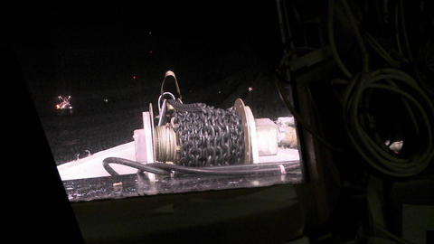 A sea vessel reels in a chain at night Footage