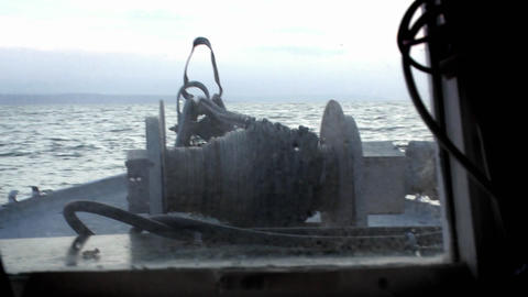 A rope is released into the water from the deck of a boat, as the captain sits at the controls Footage