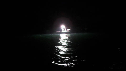 A fish-cutter works at night in the open seas Footage