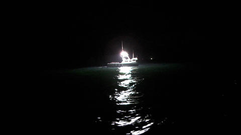 A fish-cutter works at night in the open seas Stock Video Footage