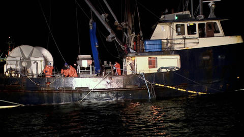 Several men work at night on a ship Footage