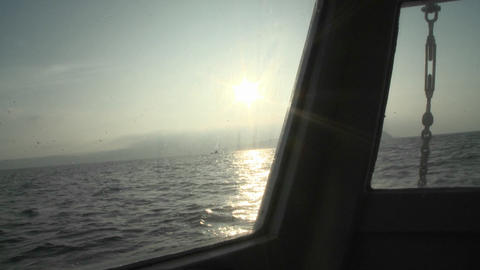 A boat rocks in the water as the sun sets Stock Video Footage