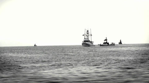 A group of boats sit together in the ocean Footage
