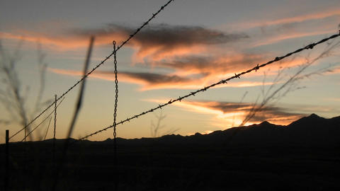 The sun sets over an area protected by barbed wire Stock Video Footage