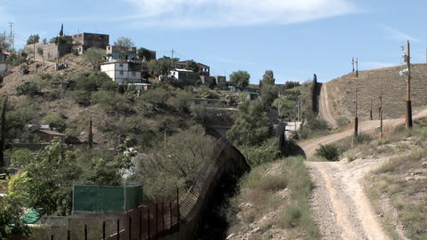 A group of buildings sits on a hillside, trees blow in... Stock Video Footage