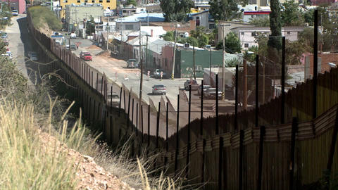 A hillside view front behind a large fence looking down on an intercity street neighborhood Footage