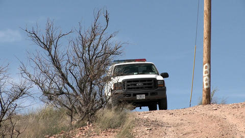 A border patrol vehicle is parked on a dirt road Stock Video Footage
