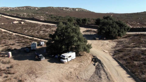 Campers are parked under a tree in a remote area Footage