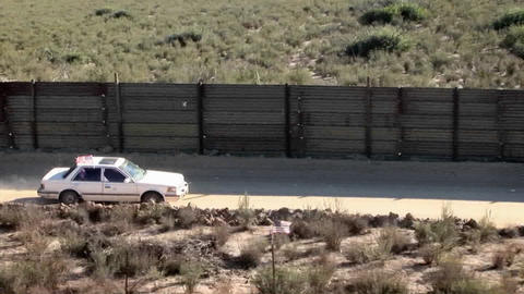 A white car with a sunroof is driving along a desert road bordered by a tall wooden fence Footage