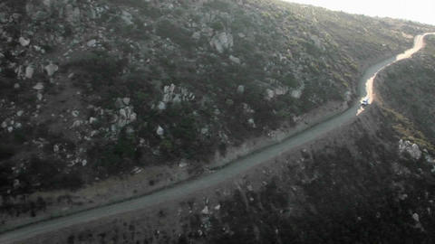 Aerial view of a border patrol vehicle on a rocky dirt road Stock Video Footage
