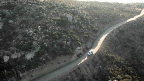 Aerial view of a border patrol vehicle on a rocky dirt road Footage