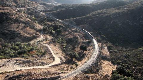 A train travels through a rough desert terrain Stock Video Footage