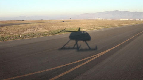 A helicopter flies over a long stretch of road Footage