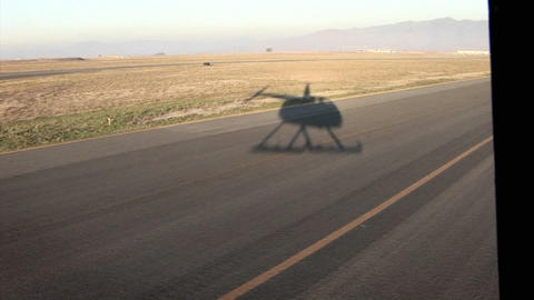 A helicopter flies over a long stretch of road Stock Video Footage