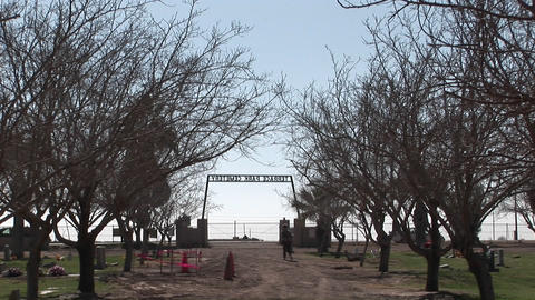 People walk around a cemetery and cars drive by Stock Video Footage