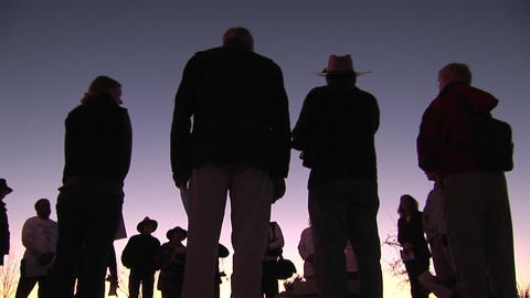 A group of people stand in a circle talking Footage