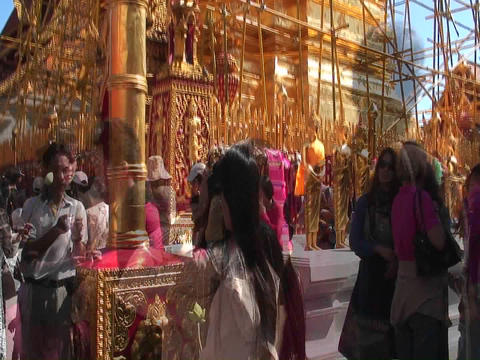 People walk back and forth in front of an ornate gold building in a time lapse sequence Footage