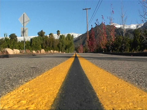 Street level view of a double yellow line on a roadway Footage
