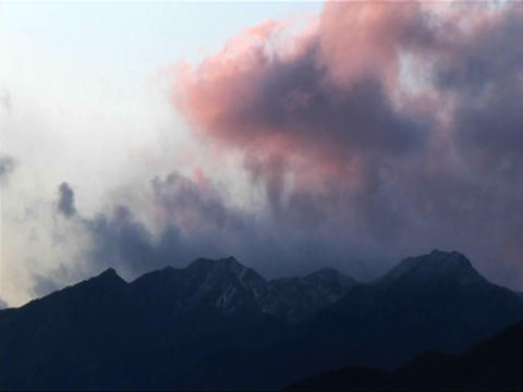Dark clouds roll over low mountains near sunset Stock Video Footage