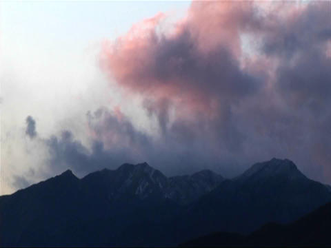Dark clouds roll over low mountains near sunset Footage