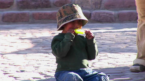 A Latin American boy sits on the ground and eats a green... Stock Video Footage