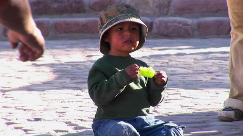 A Latin American boy sits on the ground and eats a green popsicle in a South American village Footage
