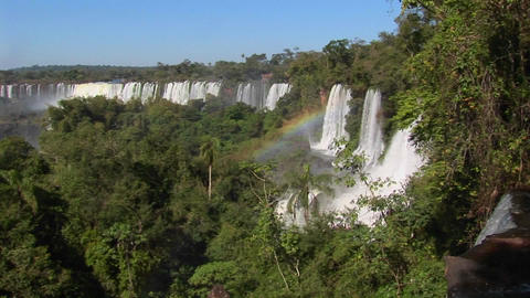 Iguacu Falls flows out of the jungle with a rainbow foreground Footage