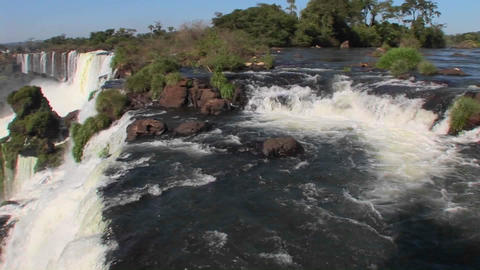 Pan across Iguacu Falls flowing out of the jungle with a... Stock Video Footage