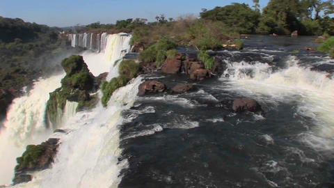 Pan across Iguacu Falls flowing out of the jungle with a rainbow foreground Footage