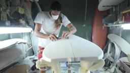 Surfboard shaping, Shaper sanding the nose of the surfboard with a sanding block Footage