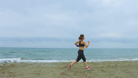 Young lady in sportswear running on the beach, taking care of body and health Live Action
