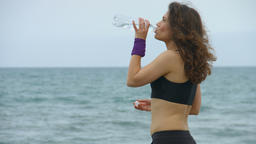 Beautiful woman in sportswear smiling, enjoying fresh water after morning run Footage
