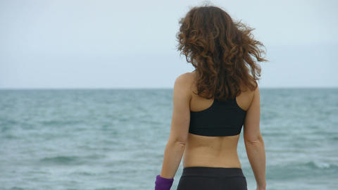 Active young woman stops to look at amazing seascape. Salty sea waves splashing Footage