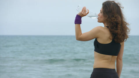 Young sportswoman feels thirsty after workout, drinking fresh water from bottle Footage
