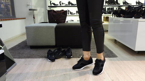 Pretty girl tie shoelaces on new sneakers in shoe store, turn before mirror Live Action