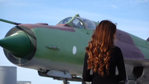 Young woman with long wavy brunette hair stand back against MiG-21 batte plane Footage