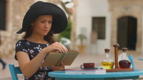 Beautiful lady turning pages of favorite book, reading interesting novel in cafe Footage