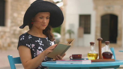 Beautiful young woman reading interesting book, marking favorite places with pen Footage